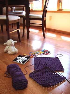 two granny squares and some baby toys